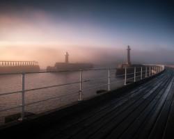 Foggy dawn Whitby pier England